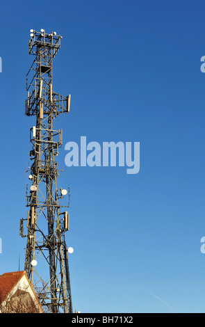 Mobile phone and communications tower taken against a clear blue sky. - Stock Photo