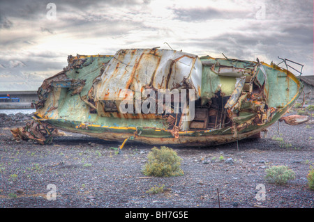 Rusty old ship abandoned near a harbor.  Vueltas area of Valley Gran Rey, La Gomera, Canary Islands - Stock Photo