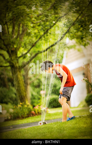 A young boy standing in a sprinkler Stock Photo: 275695506