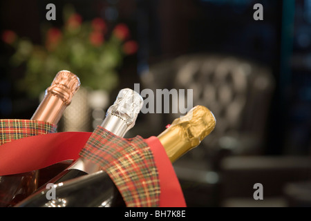 Three 3 champagne bubbles bottles one silver two gold red ribbons metal bowl blurred interior view blurred background - Stock Photo