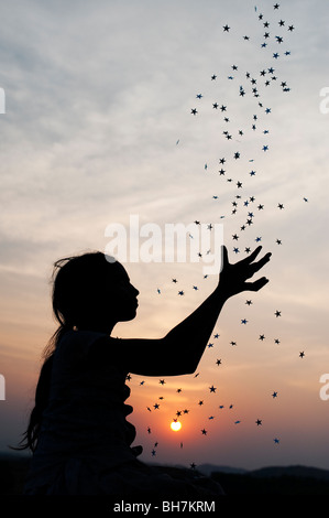 Silhouette of a young Indian girl catching falling stars at sunset. India - Stock Photo