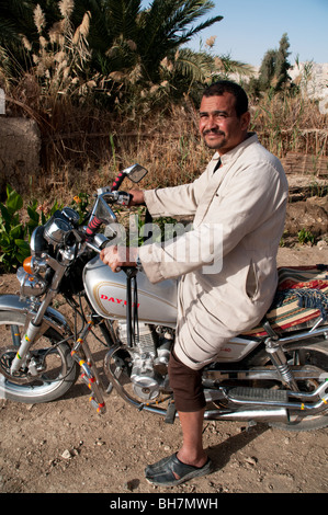 An Arab Egyptian man sitting on his motorcycle in the village of al Qasr, in Dakhla Oasis, Western Desert region, - Stock Photo