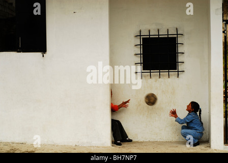 Ecuador, Latacunga, children playing with ball by a wall - Stock Photo
