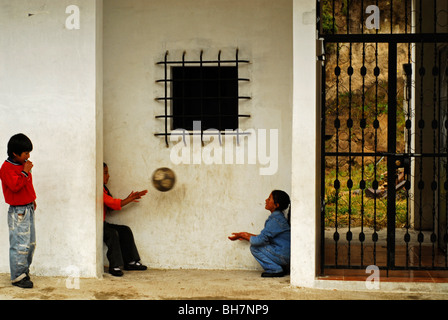 Ecuador, Latacunga, side view of children playing with a ball by the wall - Stock Photo