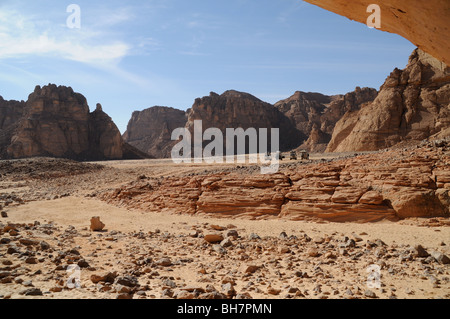 The view looking out at safari jeeps in the rocky desert, from the Cave of the Swimmers in the Gilf Kebir region - Stock Photo