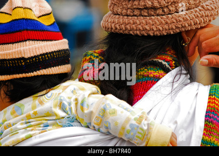 Ecuador, Otavalo, rear view of a mother with a colourful rainbow like cotton pullover carrying a baby girl wearing - Stock Photo