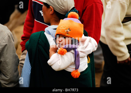 Ecuador, Otavalo, rear view of a baby wearing an orange wool cap his finger stuck in his mouth carried on the back - Stock Photo