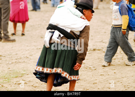 Ecuador, Otavalo, rear view of a mother wearing traditional indigenous clothes carrying a baby girl on her back - Stock Photo