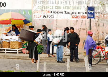 Ecuador, Otavalo, view of a group of local indigenous people standing at a market stall against an old rundown wall - Stock Photo