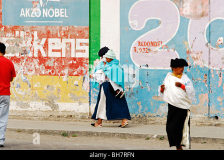 Ecuador, Otavalo, side view of an indigenous women wearing their traditional indigenous clothes walking by a wall - Stock Photo
