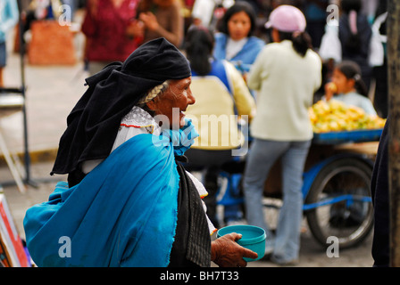 Ecuador, Otavalo, rear view of a senior woman begging in the market holding a blue plastic pot, a blue fabric wrapped - Stock Photo