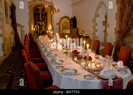 Formal seated laid and prepared candlelit banquet dinner table in luxury castle surroundings - Stock Photo