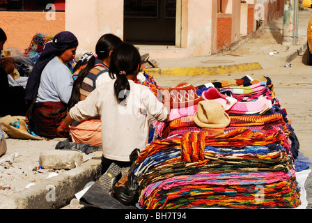 Ecuador, Otavalo, rear view of a girl sitting by stack of colourful woolen clothes on display in street market - Stock Photo