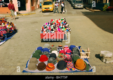 Ecuador, Otavalo, hats on display at a colourful stall in a street market with some houses in the background - Stock Photo