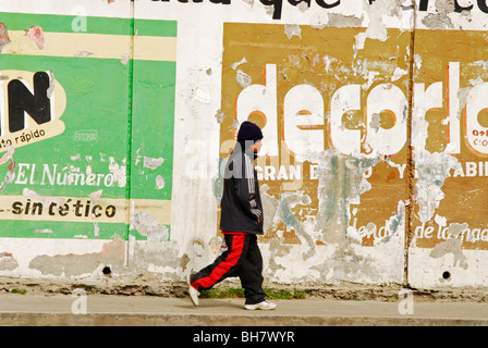 Ecuador, Otavalo, side view of a man wearing training clothes walking by a wall with decayed advertisements for - Stock Photo