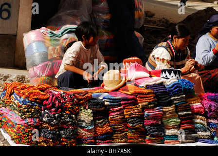 Ecuador, Otavalo, young girls sitting by stacks of colourful woolen clothes and hats on display in street market - Stock Photo