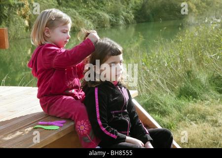 Little sister girls hairdresser on the river ourdoor park - Stock Photo