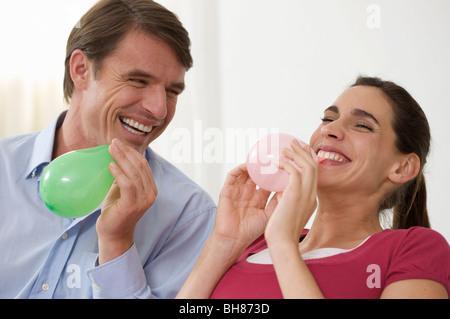 a couple having fun blowing balloons - Stock Photo