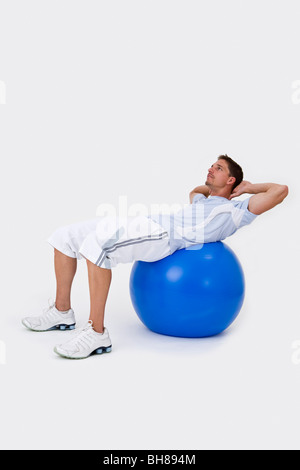 A man using an exercise ball to do sit-ups - Stock Photo