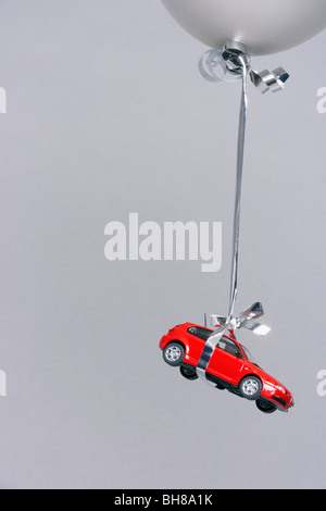 Red car carried by a grey balloon - Stock Photo