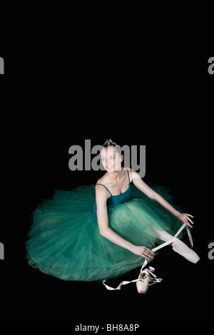 A ballet dancer wearing a costume tying her pointe shoe - Stock Photo