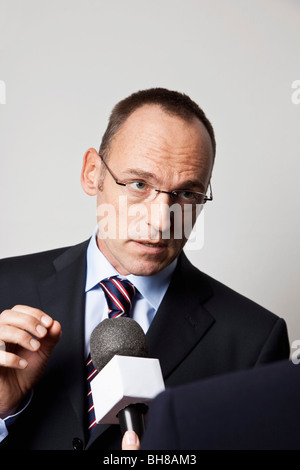 A man in a suit being interviewed - Stock Photo