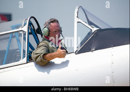 Pilot giving thumbs-up in his North American SNJ-4 – SNJ-6 fighter plane from World War II, Mid-Atlantic Air Museum - Stock Photo