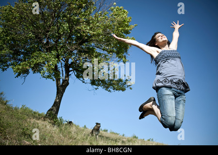 Woman leaping by tree - Stock Photo