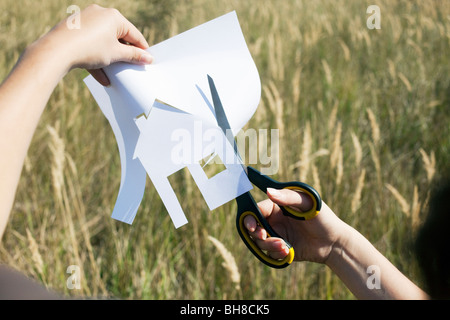 Hands cutting paper house - Stock Photo