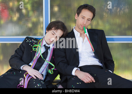two businessmen at bus stop after party - Stock Photo