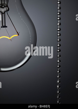 Close up on a turned on light bulb with a pull switch over a grey background. - Stock Photo