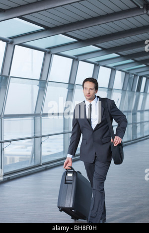 businessman with case walking in skywalk - Stock Photo
