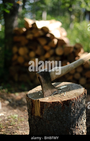 An axe stuck in a log in front of a pile of wood - Stock Photo