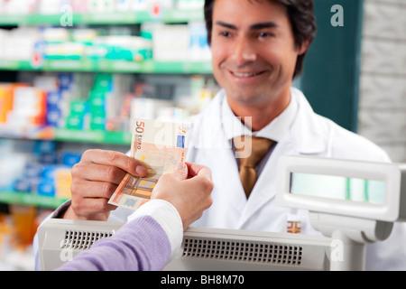 pharmacist taking 50 euros - Stock Photo