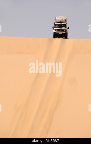 A desert safari land cruiser 4x4 jeep crests a giant sand dune in the Great Sand Sea of the Western Desert, Egyptian - Stock Photo