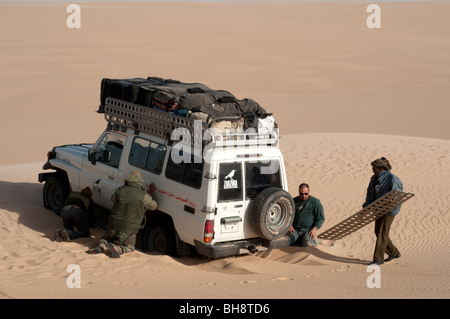 A desert safari land cruiser 4x4 jeep gets stuck in a patch of soft sand in the Great Sand Sea of the Western Desert, - Stock Photo