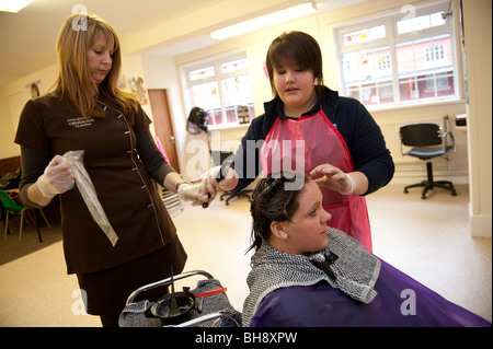 A woman vocational tutor teaching hairdressing skills to two teenage girls in secondary school, UK - Stock Photo