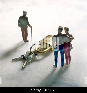 Senior citizen and couple, figurines, and keys, symbolic image for inheritance - Stock Photo