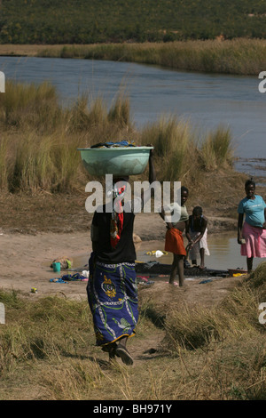 Women wash clothing in the Cuito river, Cuito Cuanavale, Angola, Africa - Stock Photo
