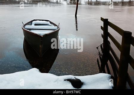 Boat in snow on Esthwaite Water, Cumbria National Park, United Kingdom - Stock Photo