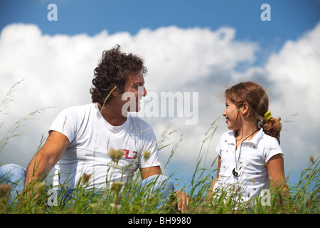 Father and daughter smiling at eachother seated in the grass in a summer day - Stock Photo