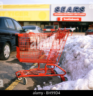 Empty red shopping cart in a snowy car park outside Sears store Fort Erie Ontario Canada - Stock Photo