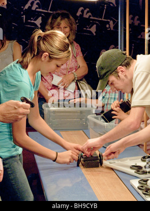 Using a hand-crank belt and toy automobile parts, visitors get the feeling of assembly line work at the Henry Ford - Stock Photo