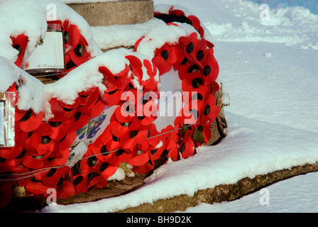 Poppies in the snow at the war memorial at St Saviour's Church, Tetbury - Stock Photo
