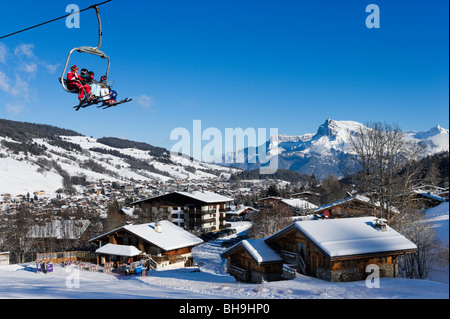 Chairlift and view over the resort from the slopes in the Rochebrune area, Megeve, Haute Savoie, France - Stock Photo