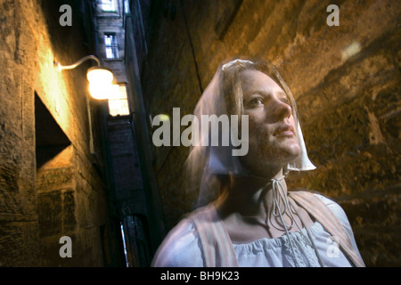 A female tour guide dressed as a 16th century character appears ghostly in an Edinburgh alley - Stock Photo