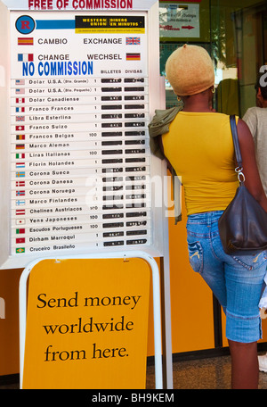 Woman leaning against international currency exchange rate board outside Western Union office in Fuengirola, Spain - Stock Photo