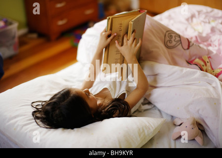Six year old girl reads book - Stock Photo