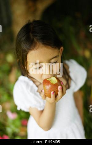 Six year old girl bites into apple - Stock Photo