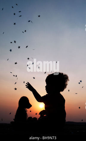Little boy catching stars with his teddy bear at sunset. Silhouette. India - Stock Photo